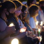 """Demonstrators pause outside police headquarters to hold """"Black Lives Matter"""" candlelight vigil"""